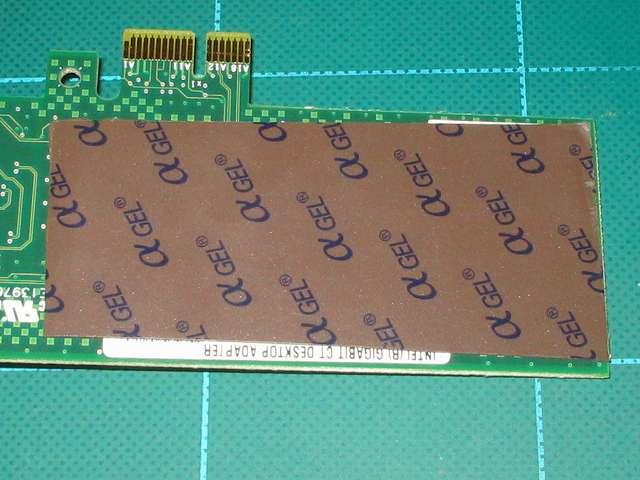 ASUS P8Z68-V PRO/GEN3 の最上段 PCI Express x1 スロットに取り付けたネットワークカード Intel Gigabit CT Desktop Adapter EXPI9301CT と Scythe グランド鎌クロス リビジョンB SCKC-2100 ヒートシンクとの接触を防ぐため余っていた αGEL をネットワークカードの基板面に貼る