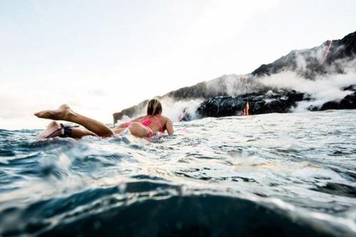 溶岩が流れ込む海岸でサーフィンの画像(12枚目)