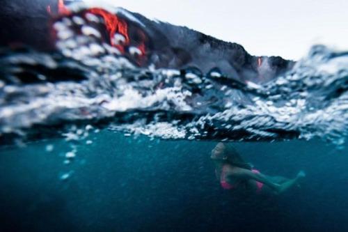 溶岩が流れ込む海岸でサーフィンの画像(13枚目)