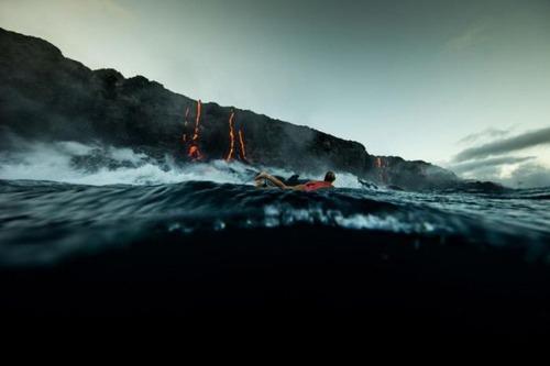 溶岩が流れ込む海岸でサーフィンの画像(15枚目)