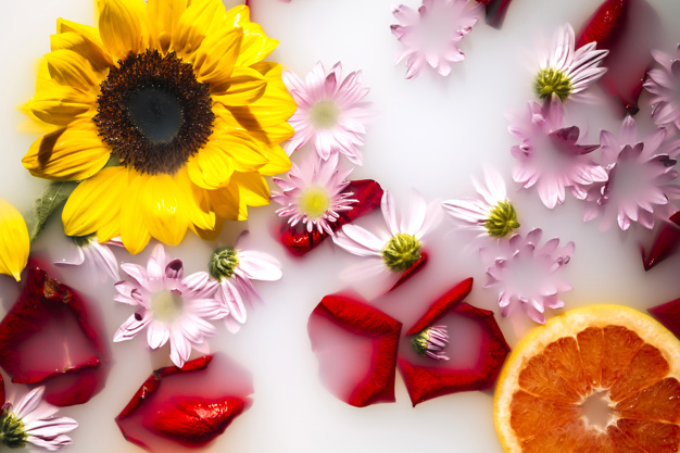 milk-bath-decorated-with-beautiful-flowers-and-grapefruit_23-2147830264.jpg