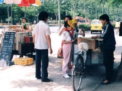 学校帰りにアイスクリームを買う小学生。左のドリンクスタンドもビール、アイス、ヨーグルト・・・等がおいている。 1993年 北京