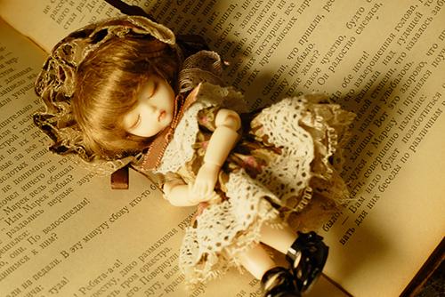 DOLL FACTORY・Baby Ariの小さな眠り目の子、Emma(エマ)。洋書の古本の上で、すやすやと眠っています。
