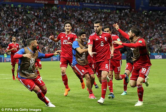 Saeid Ezatolahi (centre) wheels away in delight after thinking he has scored Irans equaliser