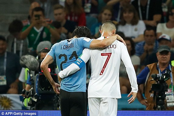 Portugals Cristiano Ronaldo helps Uruguays Edinson Cavani of the field