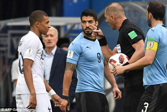 Frances Kylian Mbappe as Uruguays Luis Suarez looks on