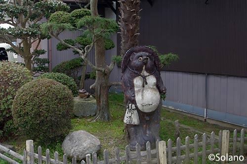 関西本線・新堂駅、旧駅舎前の植込みの中の狸の置物