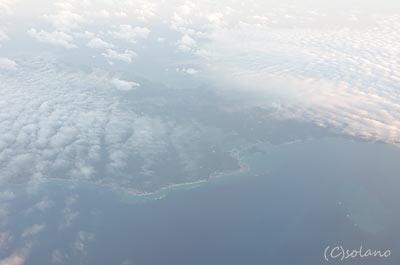 JAL沖縄那覇行きのフライトの機窓、澄んだ青い海…
