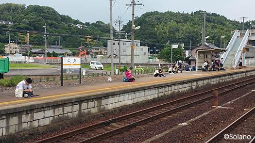 JR古井駅、プラットホームに座り列車を待つ若者の乗降客