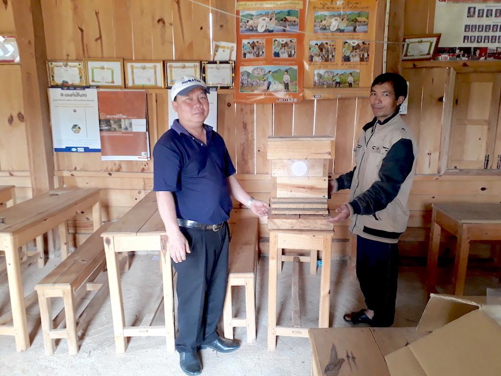 重箱式巣箱にミツバチの誘引剤を設置したシウォンさん(右)と現地スタッフのセンケオ氏