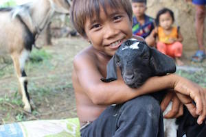 生まれた子ヤギと息子さん。メスのヤギ二匹、オスのヤギ一匹を支援しました。